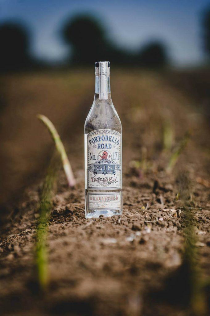 La bottiglia di Portobello Road Gin in un campo di asparagi